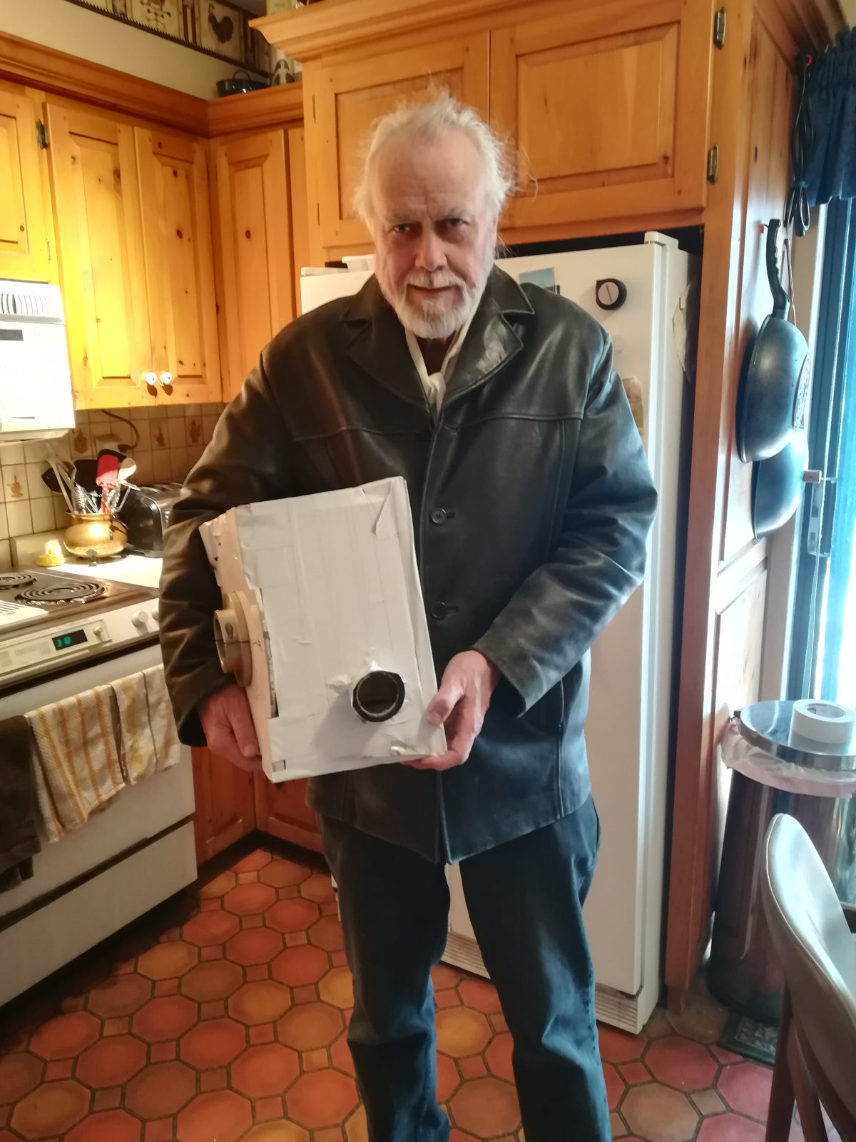Professor McElroy holding the Spectrometer in his Toronto home.