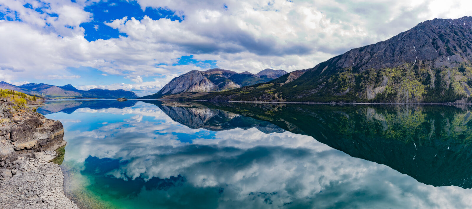 Panoramic view of calm water of Windy Arm of Tagish Lake near Carcross, Yukon Territory, Canada, with surrounding mountains mirrored on lake surface