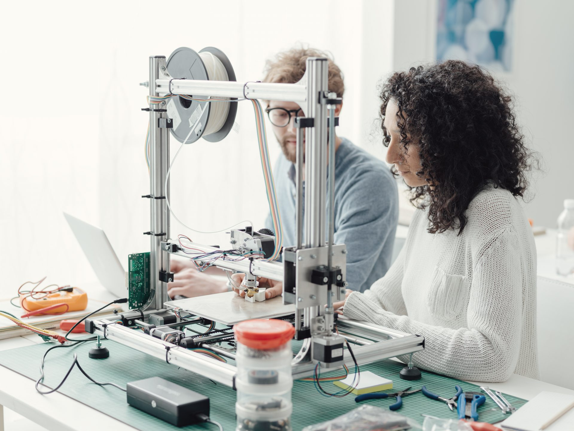 Engineering students using a 3D printer