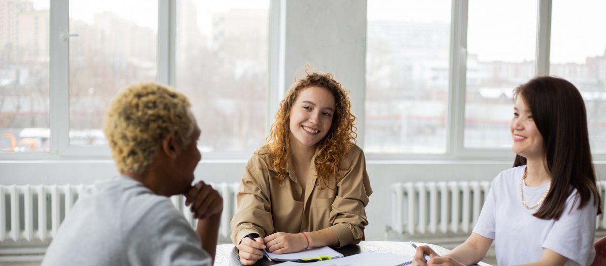 Three women speaking around a table