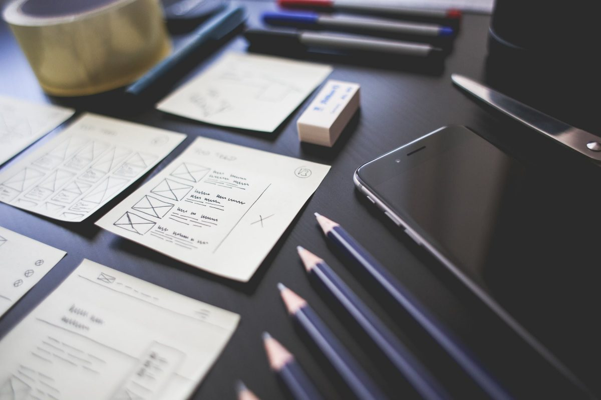desk with pens, pad of paper, phone