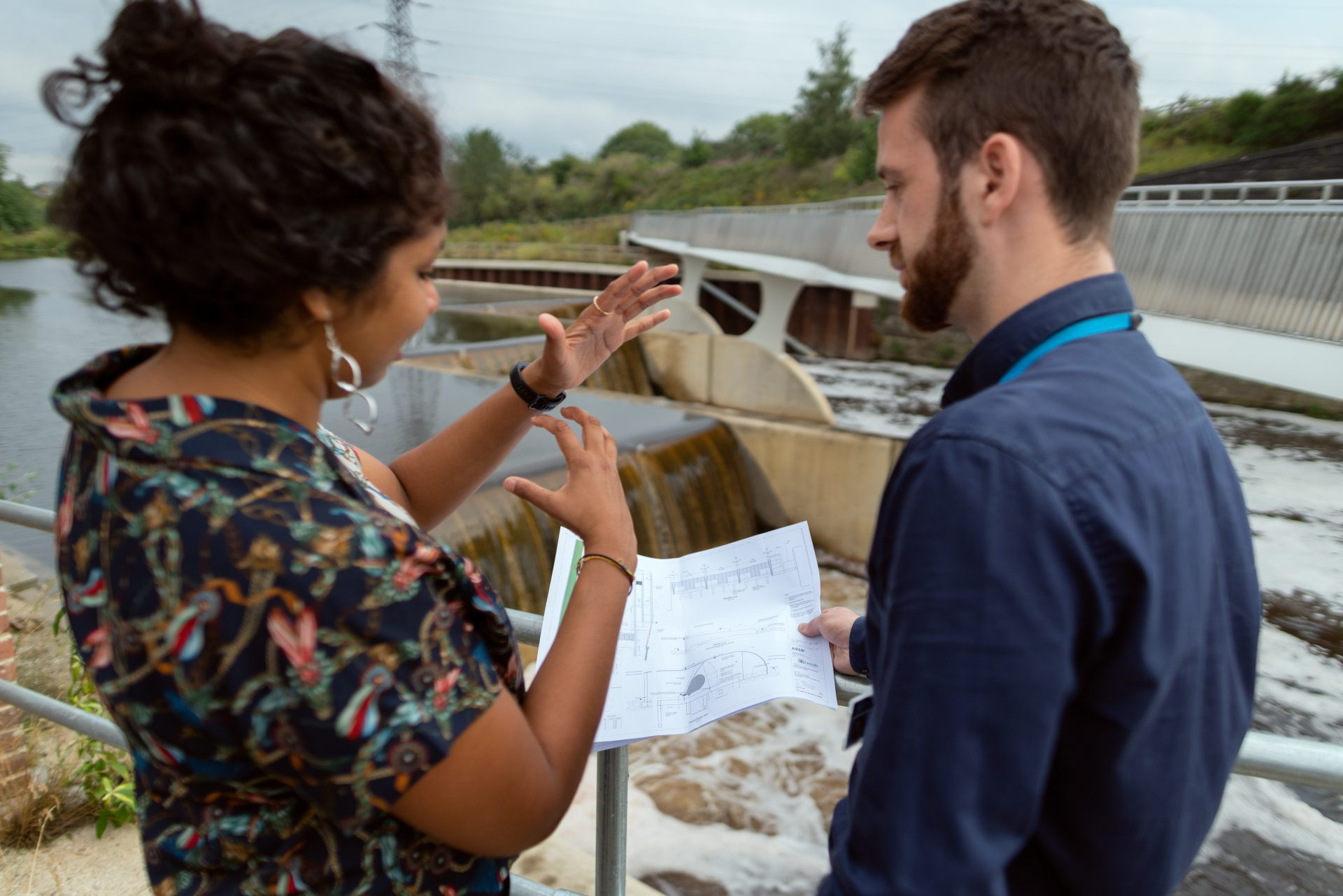 Two people look at schematics in front of a dam
